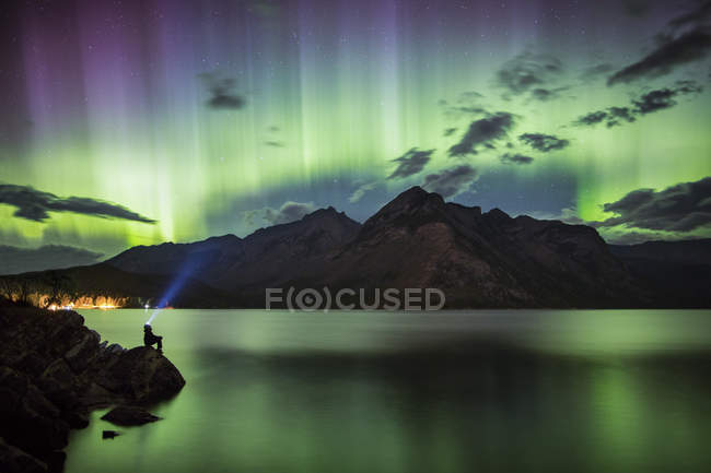 Silhouette of person sitting on rock near lake with northern lights — Stock Photo