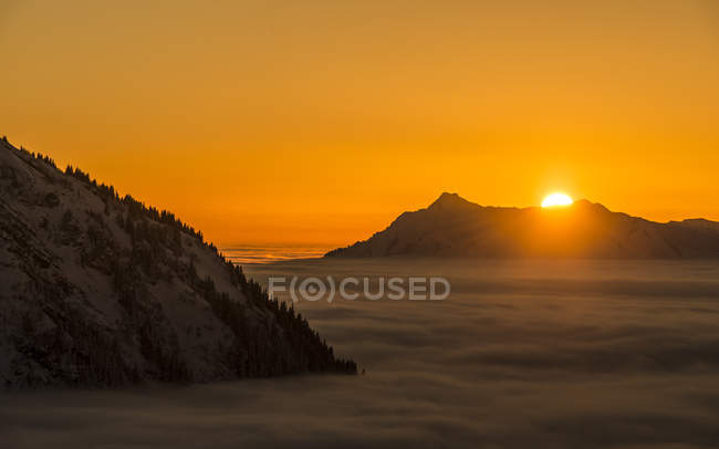 Mountain peaks surrounded by clouds during sunset — Stock Photo