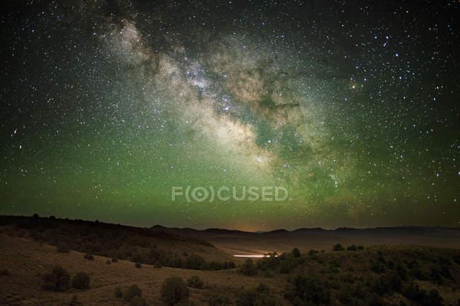 Milky Way stars glowing in night sky over hills — Stock Photo