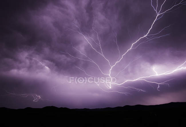Lightning Storm in cloudy sky over mountains — Stock Photo