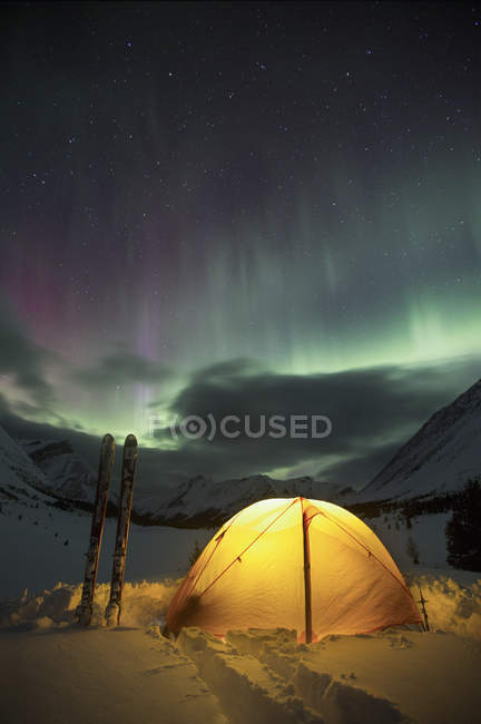 Northern lights in sky above tent glowing from inside — Stock Photo