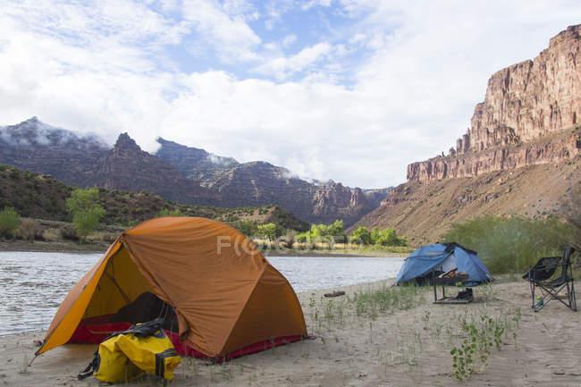 Campeggio sulla riva del fiume con vista montagne — Foto stock