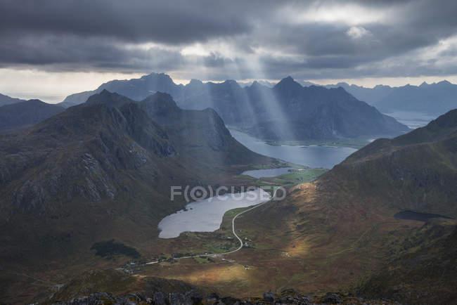 Raios de luz que brilha sobre Storvatnet lago rodeado por montanhas — Fotografia de Stock