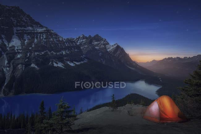 Tente posée près du lac peyto et montagnes couronnées de neige au crépuscule — Photo de stock