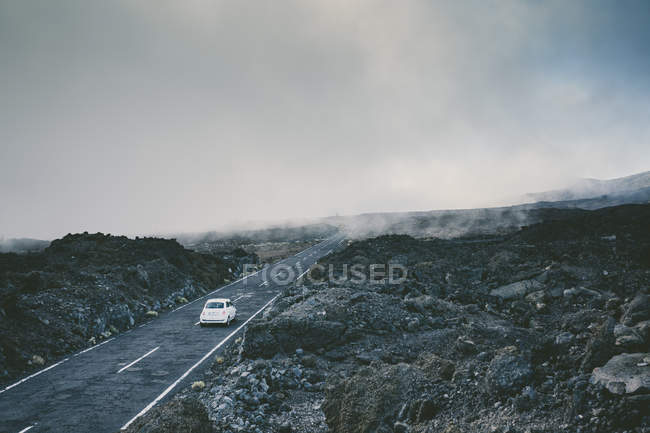 A Car Riding On A Misty Road Surrounded By Volcanic Rocks — Stock Photo