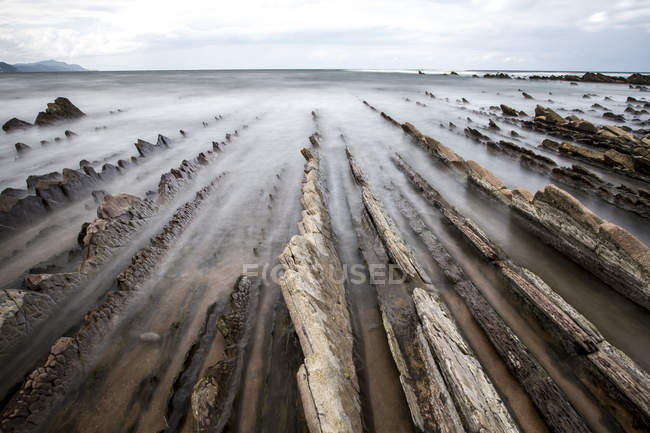 Long exposure shot of flowing water and rock formations on shore — Stock Photo