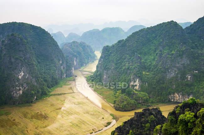 Montagne coperte di verde con campi e fiume — Foto stock