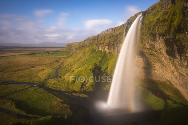 Long exposure shot of flowing waterfall with rainbow in sunlight — Stock Photo