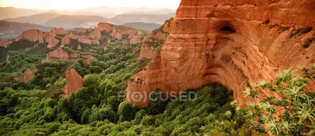 Red rocky mountains surrounded with lush greenery — Stock Photo