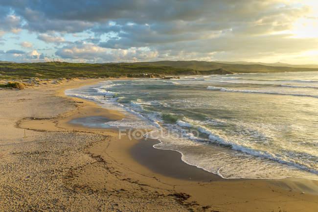 Surf waves on sandy beach with illuminated cloudy sky — Stock Photo
