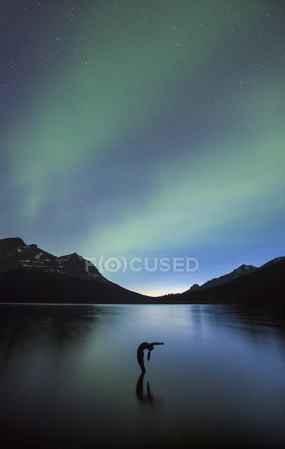 Silhouette of Person in yoga pose under aurora borealis sky — Stock Photo