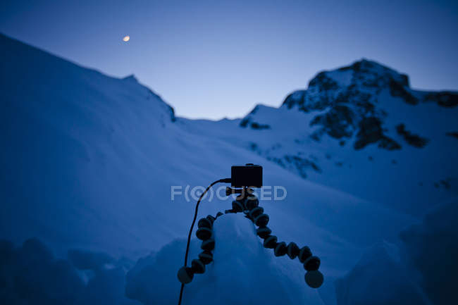 Camera on tripod in snowy mountain landscape — Stock Photo