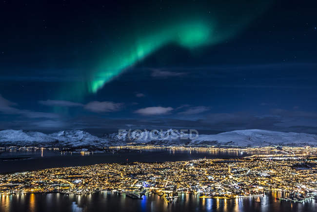Північні світло, що сяє над міста Тромсе і сніг покриті гори — стокове фото