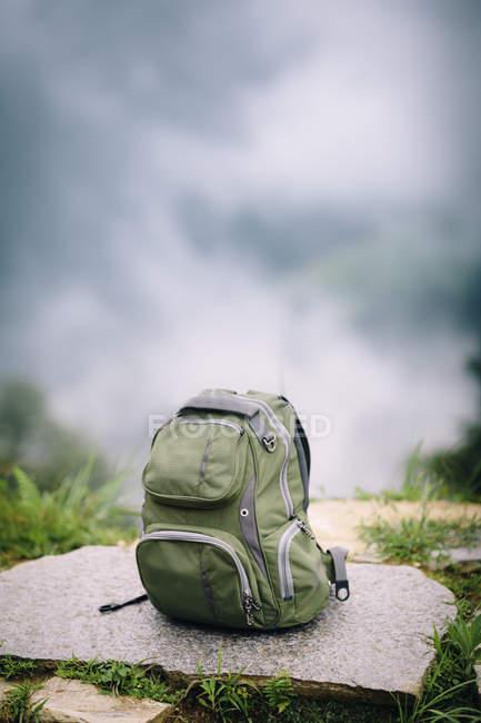 Подорожі рюкзак на пагорбі з розмитими хмари — стокове фото