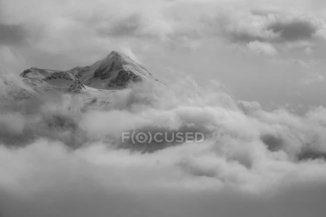 Заснеженные вершины, рост через тяжелые облака — стоковое фото