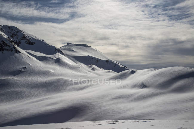 Snowcapped mountains with cloudy sky in bright sunlight — Stock Photo