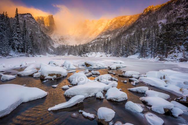 Lac de rêve avec soleil et rochers enneigés éclairé des montagnes sur fond au lever du soleil — Photo de stock