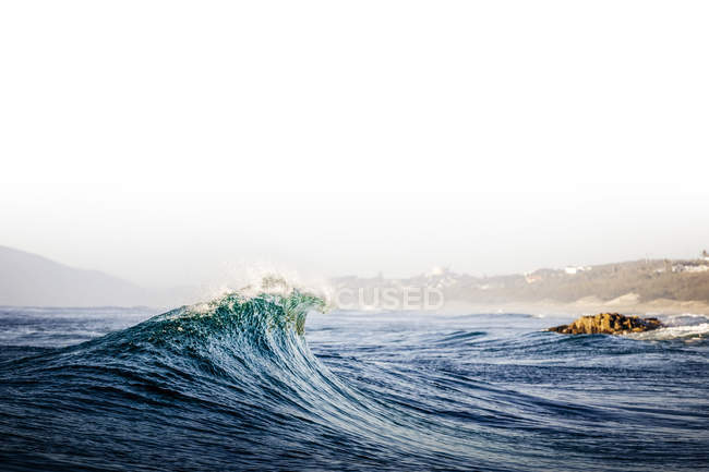 Wave breaking near shore along coastline — Stock Photo