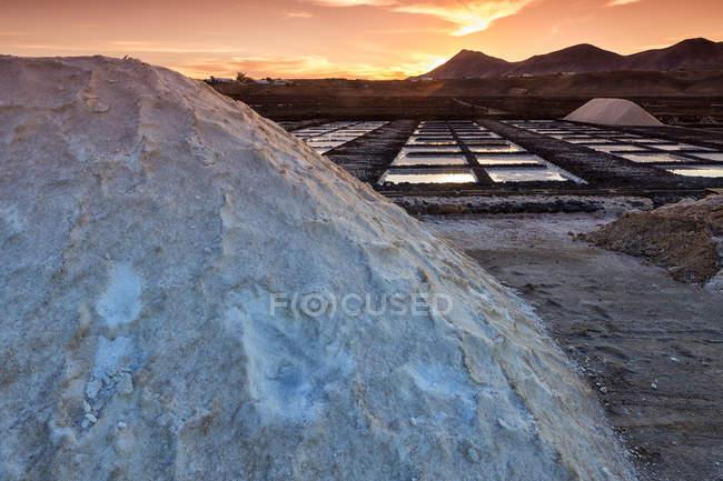 Bacias de sal sob o céu do sol, com montanhas no fundo — Fotografia de Stock