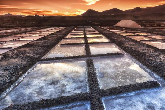Bassins de sels sous un ciel coucher de soleil avec les montagnes en arrière-plan — Photo de stock