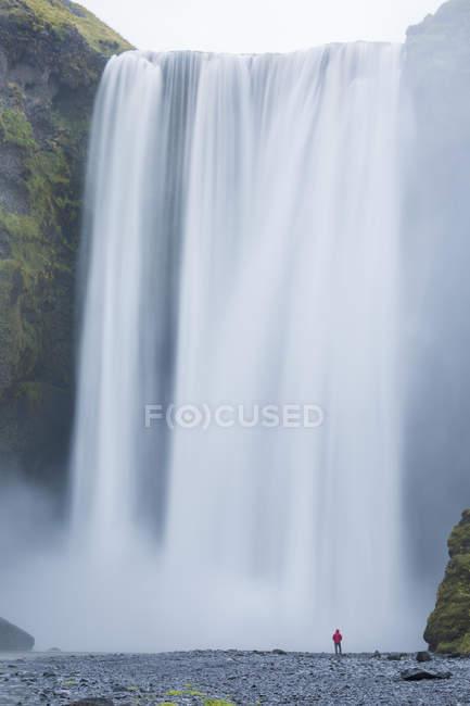 Longue exposition coup de cascade qui coule avec randonneur permanent — Photo de stock