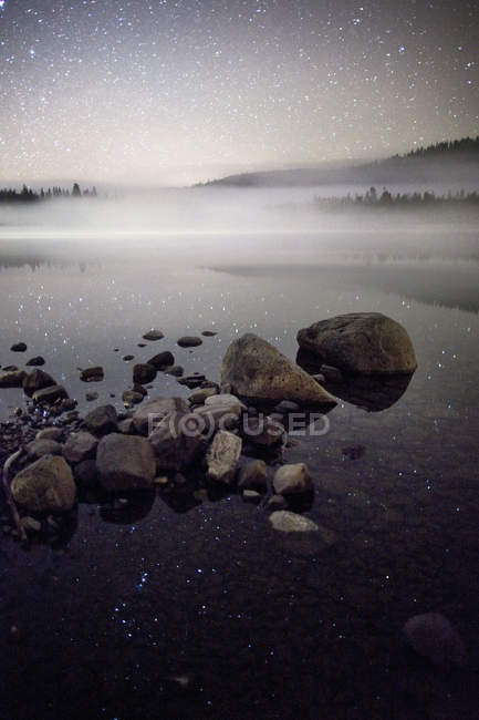 Fog and starry sky with reflection in lake water — Stock Photo