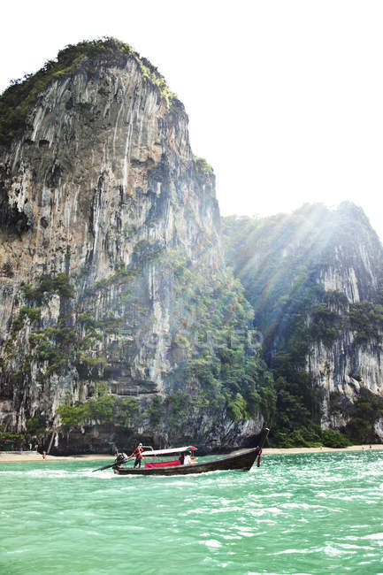 Longtail boat transporting group of people next to huge limestone cliffs and turquoise water to Railay Beach, Thailand — Stock Photo