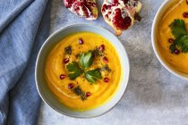 Top view of bowls of pumpkin soup with pomegranate seeds on marble surface — Stock Photo