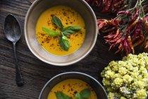 Керамические чаши вегетарианский суп с базиликом листья на деревянный стол — стоковое фото