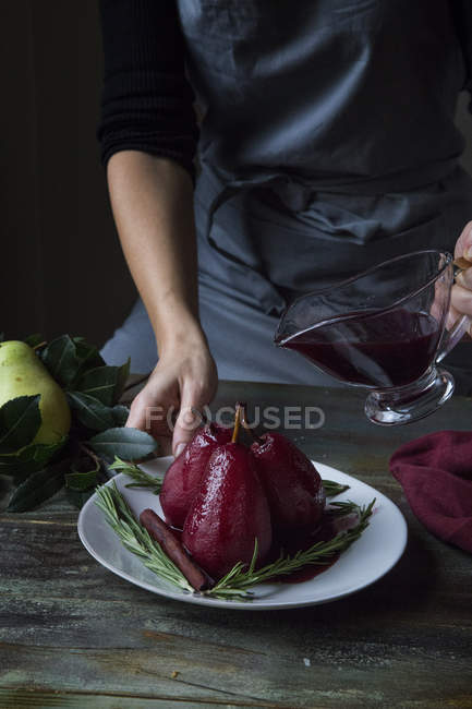 Partial view of woman pouring spiced red wine poached pears — Stock Photo