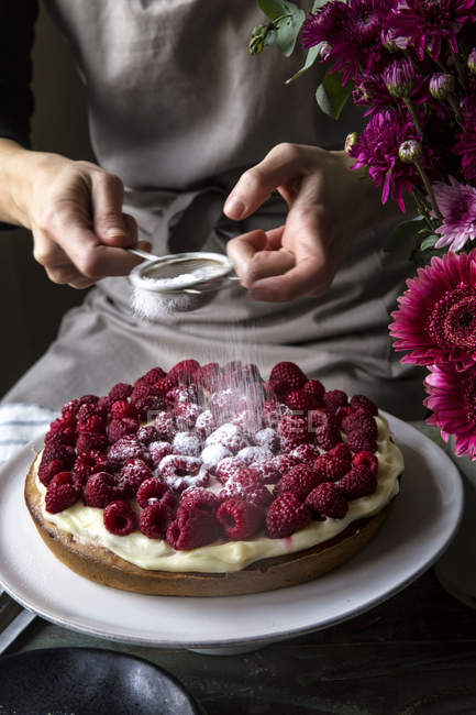 Partial view of female hands sprinkling icing sugar on cardamom cake with raspberries — Stock Photo