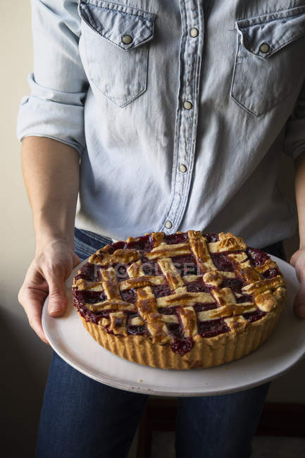 Cropped image of woman holding berry pie with a lattice top — Stock Photo