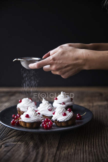 Cropped image of female hands sprinkling icing sugar on freshly baked cupcakes decorated with red currants on plate — Stock Photo