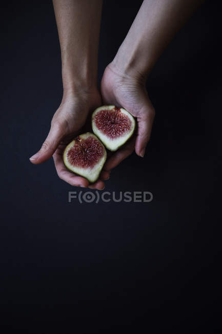 Female hands holding halved fig in hands against black background — Stock Photo