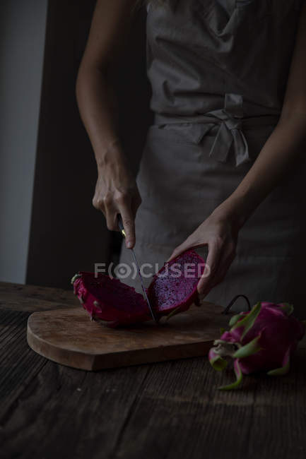 Cropped image of woman slicing dragonfruit on chopping board — Stock Photo