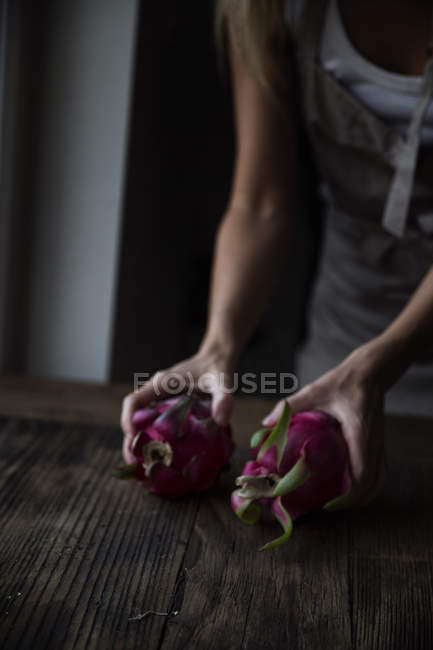 Cropped image of woman holding dragonfruits in hands on wooden table — Stock Photo
