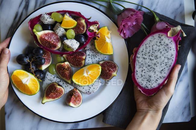 Composição de frutas fatiadas contém com figos, dragonfruit, uva e laranjas no prato — Fotografia de Stock
