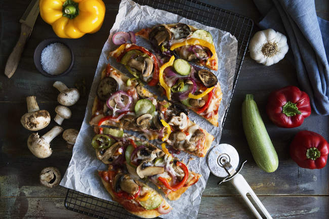 Top view of veggie pizza on cooling rack with vegetables on table — Stock Photo
