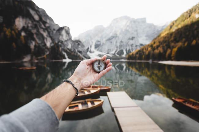 Bussola della holding della mano maschio con lago e rocce sul fondo — Foto stock