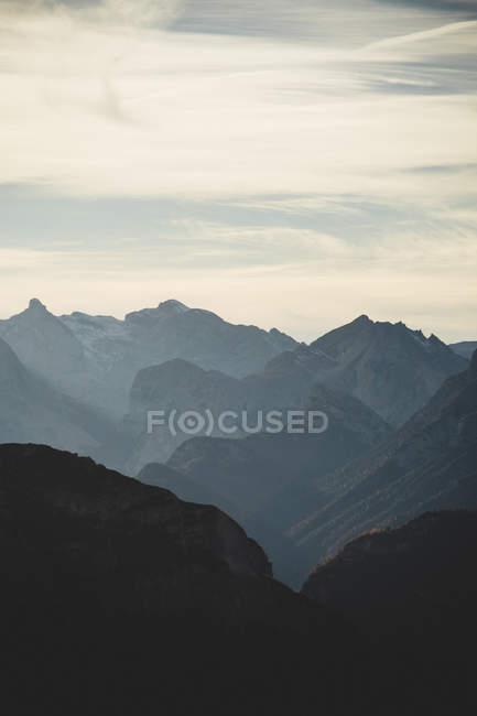 Picchi di montagna rocciosa sotto il cielo nuvoloso — Foto stock