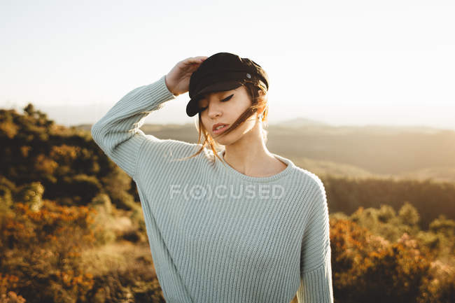 Young woman wearing cap posing in sunlight — Stock Photo