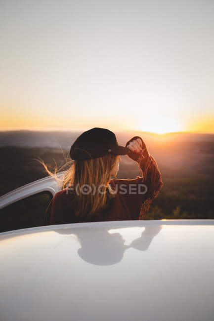 Woman holding cap visor beside car during sunset — Stock Photo