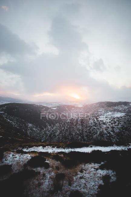 Coucher de soleil nuageux au-dessus de montagnes aux sommets enneigés — Photo de stock