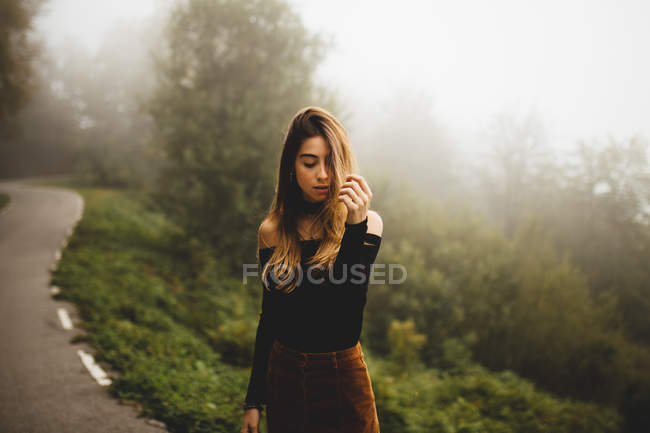 Young woman posing touching hair and looking down — Stock Photo