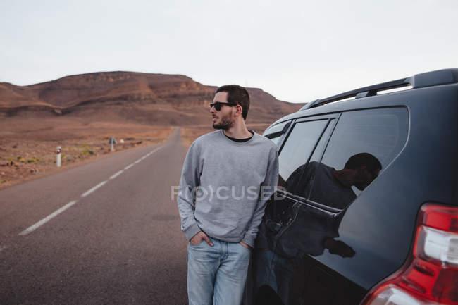 Homme debout à côté de la voiture dans le paysage de montagne — Photo de stock