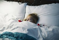 Adorable little girl lying in bed under the blanket and waiting for Santa Claus — Stock Photo