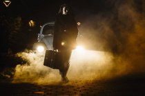 Women with suitcase in front of the car with smoke — Stock Photo