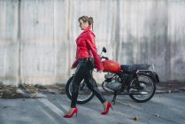 Motorbike woman walk alongside the motorcycle — Stock Photo