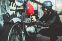 Mulher de moto arranja motocicleta danificada — Fotografia de Stock