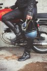 Helmet and goggles in the hand of the motorbike woman — Stock Photo